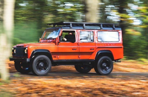 Land Rover 110 restored in red driving in forest